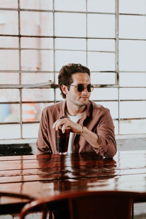 Homme en t-shirt blanc, veste marron et lunettes de soleil en train de boire un verre à une table