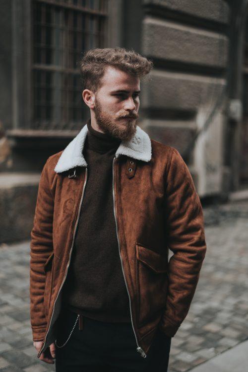 Homme avec un blazer en cuir marron et un sweat noir