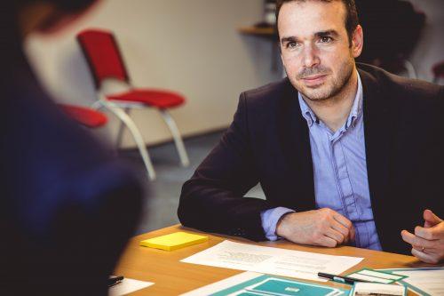 homme assis devant un bureau avec des papiers portant une chemise bleue et une veste de costume sombre